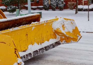 Snow plow is shown clearing a city street.